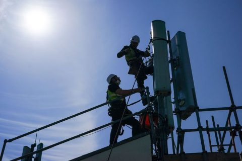 Engineers replace a Huawei network antenna in Hull, England